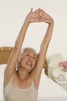 Senior Asian woman stretching in bedroom