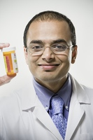 Indian male pharmacist holding medication bottle