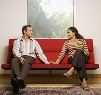 Couple smiling at each other on sofa