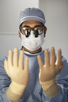Male surgeon wearing binocular loupes and looking at gloved hands