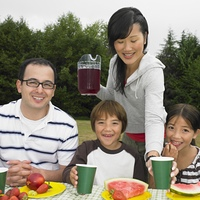 Multi-ethnic family eating at picnic table