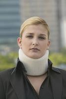 Hispanic businesswoman wearing neck brace