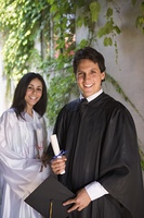 Graduating man and woman holding diplomas