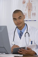 Male doctor writing in notebook