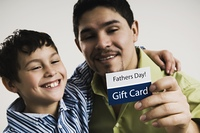 Hispanic father and son with Father's Day gift card