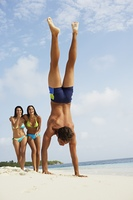 South American man doing handstand on beach