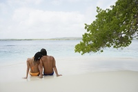 South American couple sitting on beach