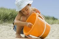 Hispanic boy with pail and shovel at beach
