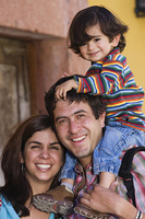 Hispanic family with son on father's shoulders
