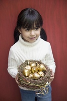 Hispanic girl holding nest with golden fruit