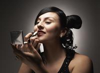 Hispanic woman applying lipstick with compact mirror