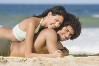 Multi-ethnic couple laying on beach