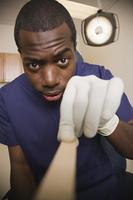 African doctor examining patient with tongue depressor