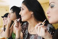 Hispanic woman applying makeup in bathroom