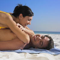 Woman laying on boyfriend at beach