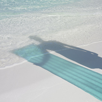 Shadow of person holding pool raft at beach