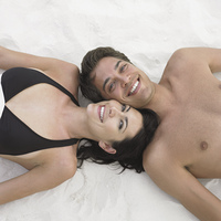 Couple laying in sand at beach