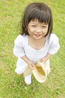 麦わら帽子を手に持つ女の子