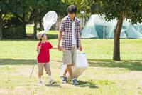 キャンプ場を手を繋いで歩く父親と息子
