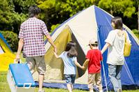 キャンプ場で手を繋いで歩く家族