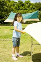 キャンプ場でテーブルクロスを敷く女の子
