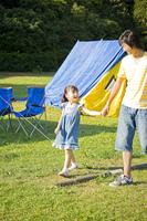 手を繋ぎキャンプ場を歩く父と娘