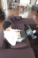 ソファに座ってノートパソコンを使う男性