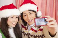クリスマスにデジカメで自分達を撮影するカップル