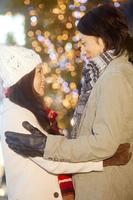 クリスマスイルミネーションバックに見つめ合うカップル