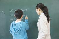 黒板の問題を解く小学生男子と横に立つ女性教師