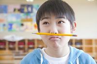 口と鼻の間に鉛筆を挟む小学生男子