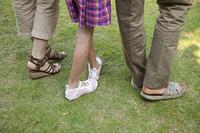 芝生を歩く親子の足元