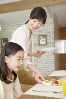 娘の朝食を運ぶ母親