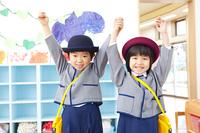手を繋いで両手を挙げる幼稚園児男女