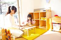 おままごとをする幼稚園女児と幼稚園教諭