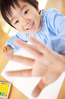 クレヨンで絵を描く幼稚園男児