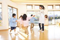 輪になって踊る幼稚園教諭と幼稚園児