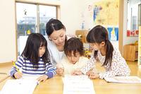 知育ドリルをする保育園児3人と保育士