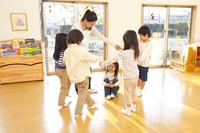 輪になって踊る保育士と保育園児