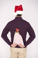 プレゼントを背中に隠している男性