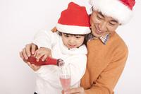 シャンパンをグラスに注ぐ父と娘