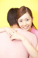 笑顔で男性を抱きしめる女性