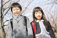 桜並木の下に立つ小学生男女