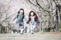 桜並木を走る小学生男女