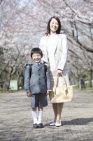 桜並木の下に立つ小学生男子と母親