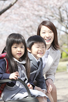 桜の下に座る小学生男女と母親
