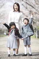 桜並木の下でガッツポーズをとる小学生男女と母親
