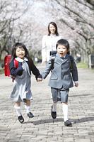 桜並木を走る小学生男女と後ろから歩く母親