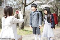 桜並木の下で子供達を撮影する母親