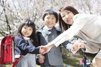 桜の下で手をつなぐ小学生男女と母親